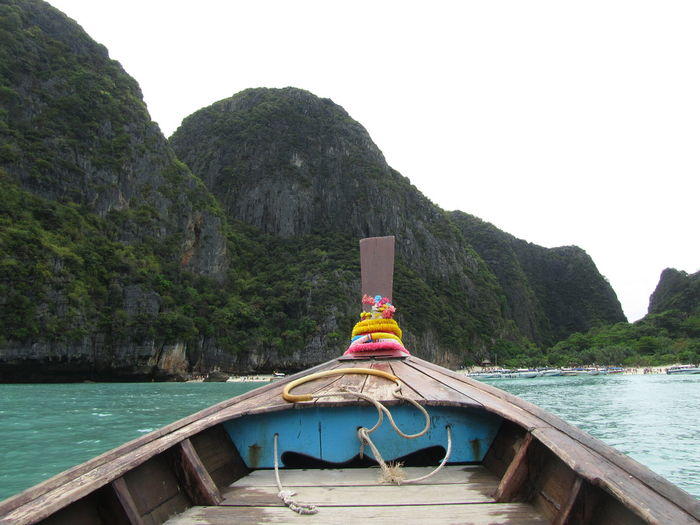 Longtail boat in sea against rocky mountains at krabi province