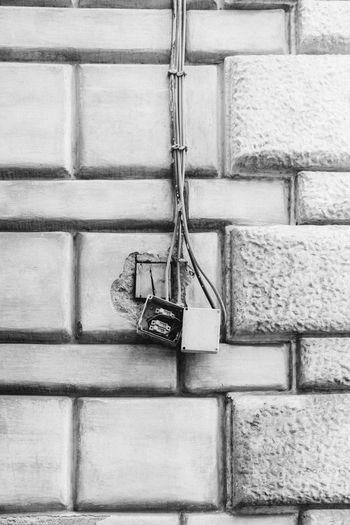 Damaged electric socket on brick wall