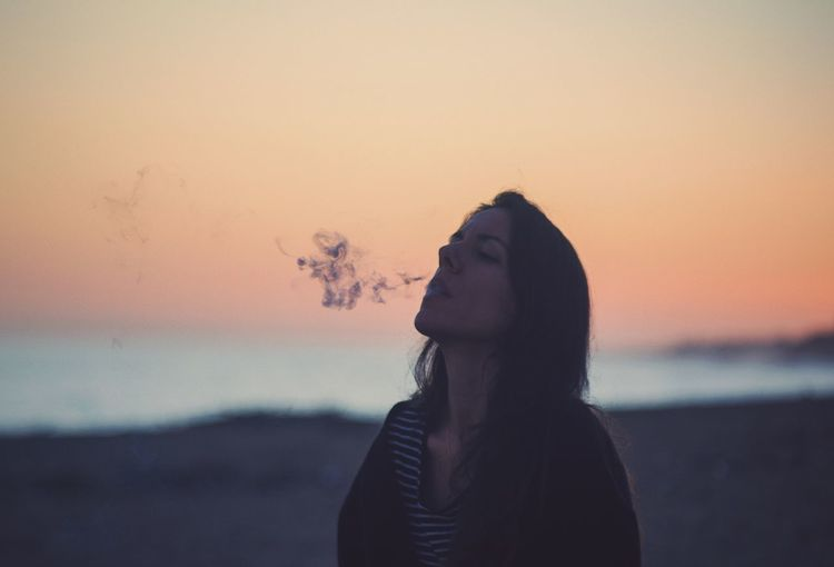 Mature woman smoking while standing at beach against sky during sunset