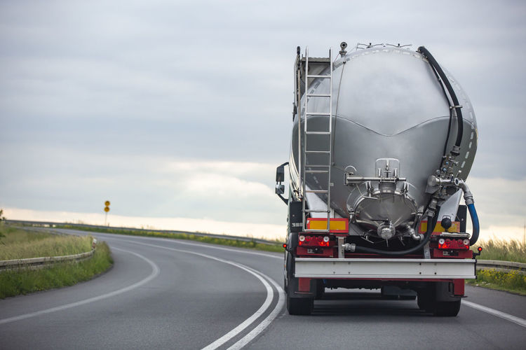 View of truck on road against cloudy sky