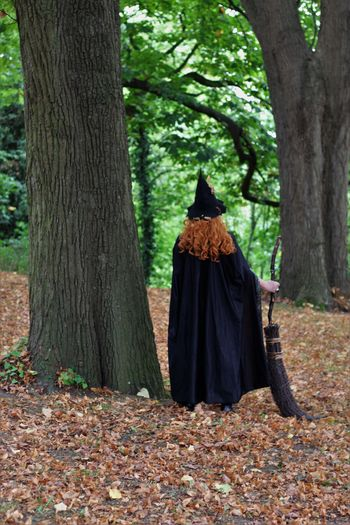 Rear view of witch holding broom standing in forest