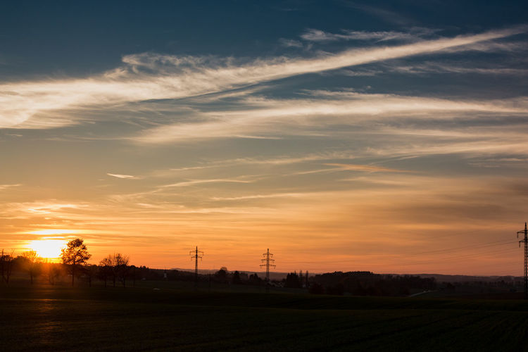 Silhouette of electricity pylon on field against sky at sunset