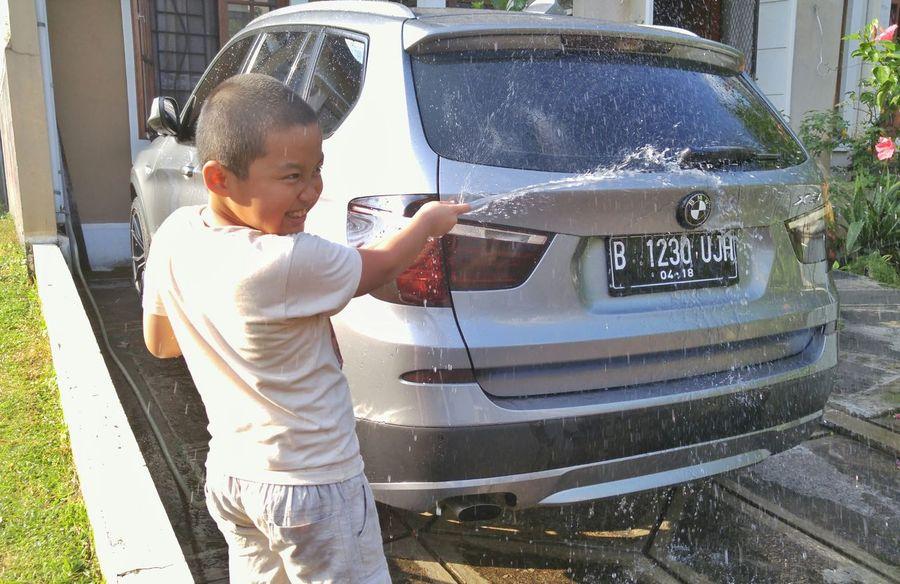 Asian kid washing a car Asian  Kid Helping Carwash Carwashing Child Water Fun Happiness Summer
