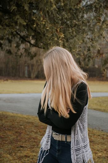 Woman with blond hair standing in park during autumn