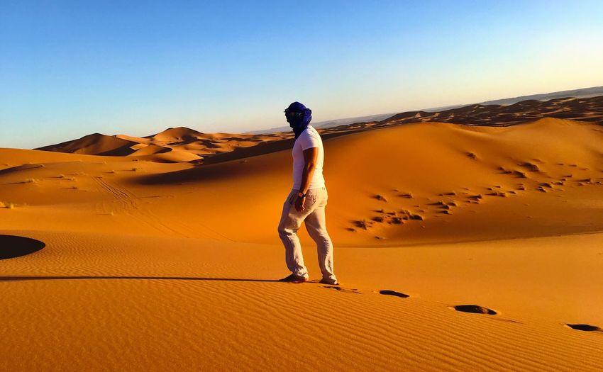 Full length of woman walking on sand dune against sky