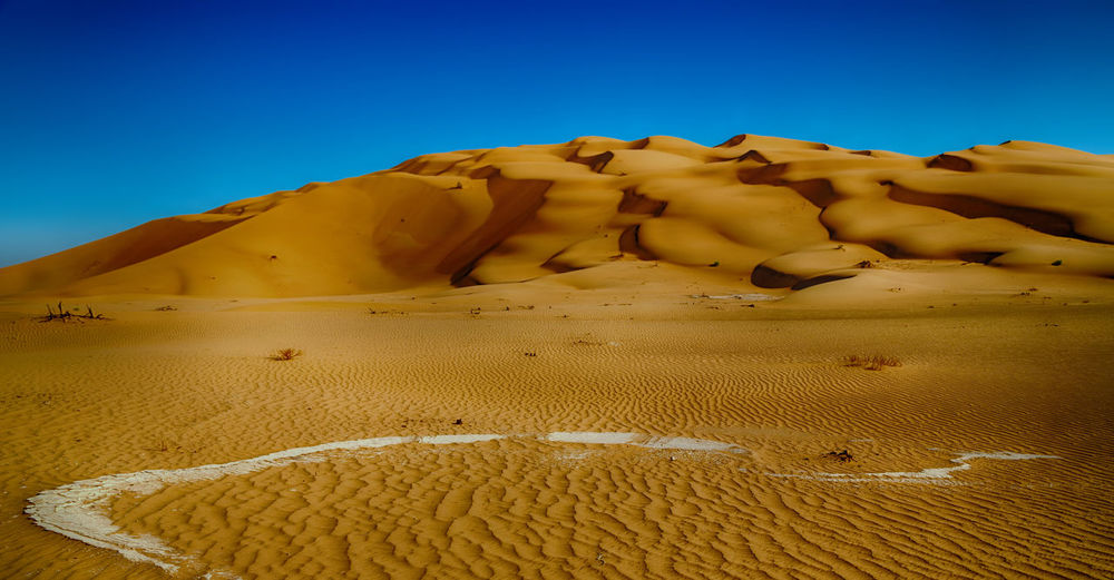 Sand dune in desert against clear blue sky