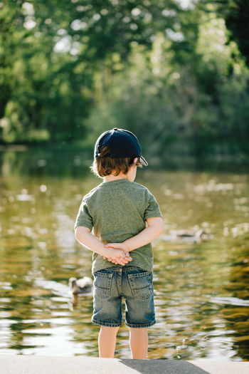 Watching the ducks Fun Pond Sunlight Boy Casual Clothing Child Childhood Day Ducks Lake Leisure Activity Lifestyles Nature Outdoors Real People Rear View Shorts Standing Summer Warm Water