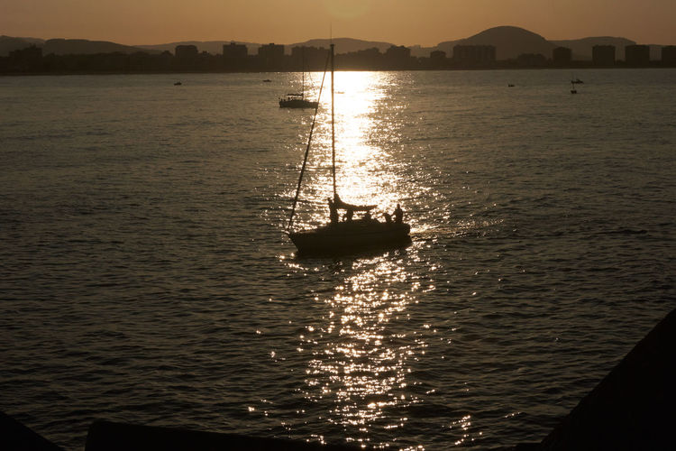 Silhouette sailboat in sea against sky during sunset