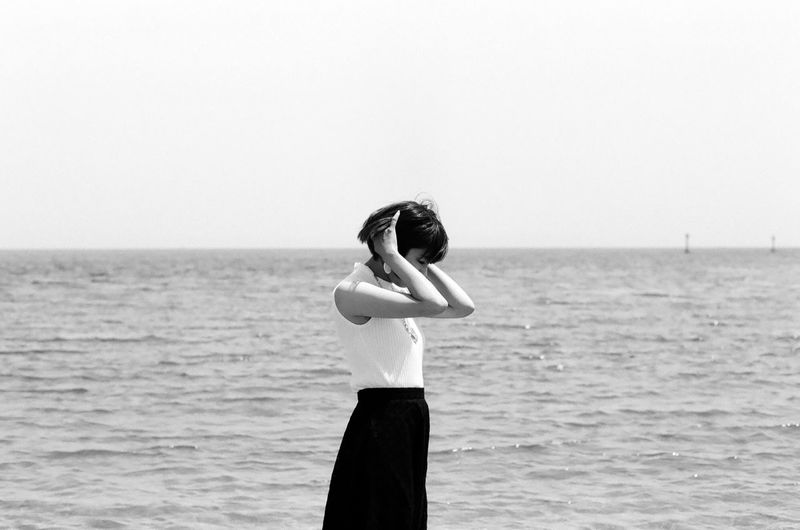 Side View Of Young Woman Standing At Beach Against Sky During Sunny Day