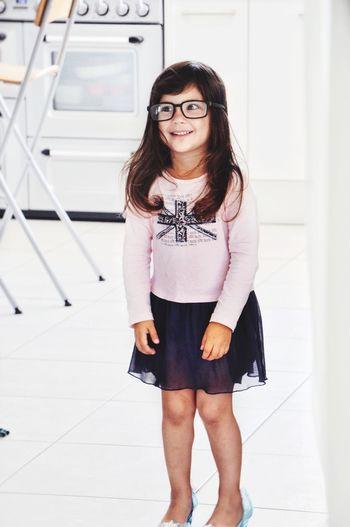 Happy girl in casuals standing in kitchen