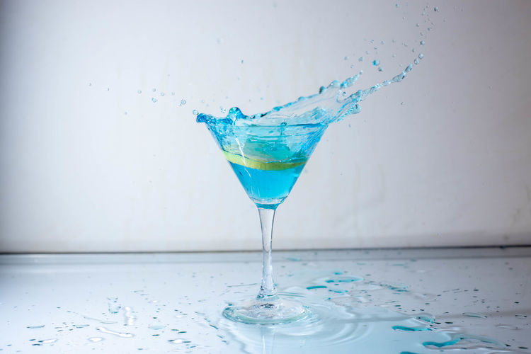 Close-up of glass of water on table against white background