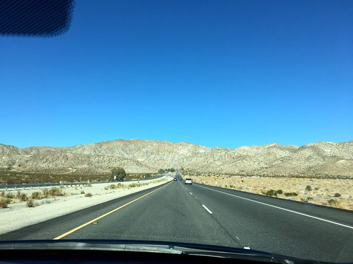 Transportation Road Car The Way Forward Vehicle Interior Windshield Car Interior Land Vehicle Car Point Of View Copy Space Road Marking Clear Sky Mountain Day Highway Mode Of Transport Landscape No People Road Trip Blue