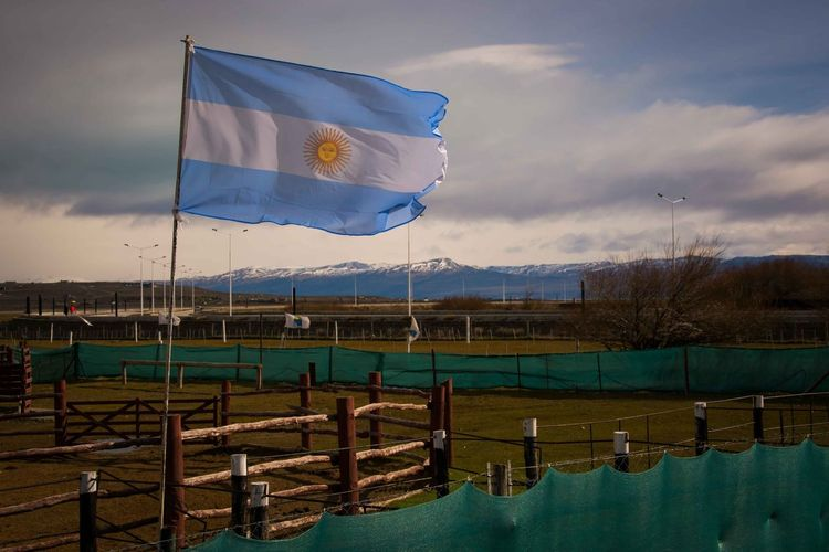 An Argentinian flag moves with the wind, in El Calafate, Santa Cruz, Argentina. Cloud - Sky Day Flag Horizontal Nature No People Outdoors Patriotism Reflection Sky Water
