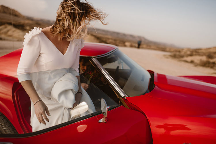 Rear view of woman sitting on car