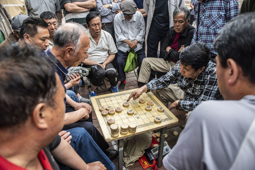Adult Arts Culture And Entertainment Chinese Chess Communication Crowd Game Group Group Of People High Angle View Large Group Of People Leisure Activity Leisure Games Looking Men Play Playing Real People Sitting Togetherness