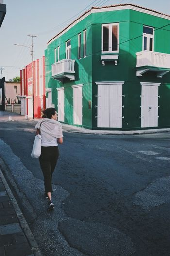 Rear view of woman walking on road by building