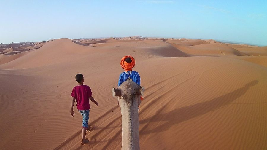 Sand Desert Sand Dune Arid Climate Rear View Landscape Two People Full Length Outdoors Day Scenics Real People Nature Boys Adventure Travel Destinations Physical Geography Togetherness Sky Standing Travel Traveling Travel Photography Morocco EyeEmNewHere