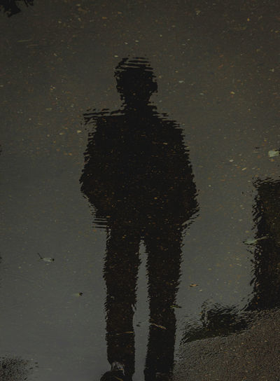 Reflection of silhouette person on puddle in lake