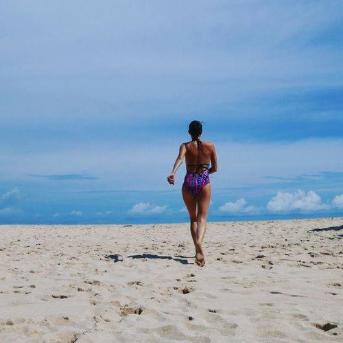 Full length rear view of woman in swimwear walking at beach against sky