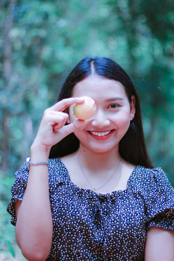 Portrait of smiling woman holding fruit