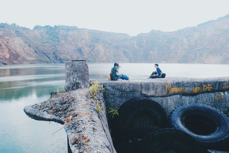 Friends sitting on retaining wall by river