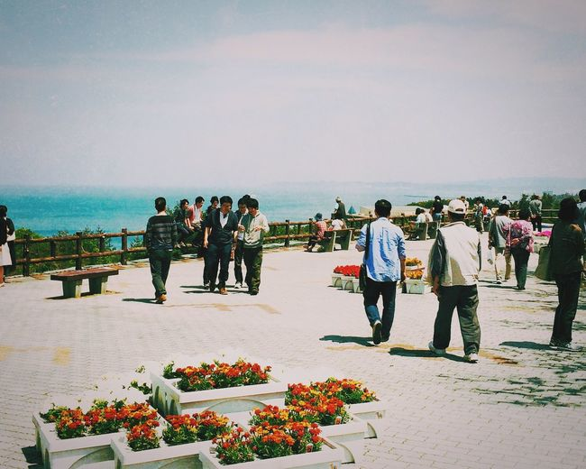 People On Walkway By Sea With Large Flower Pots On Foreground
