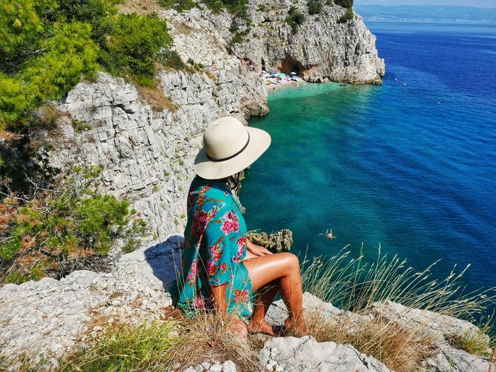 Woman sitting on rock by sea. view, cliff, summer, vacation, travel.