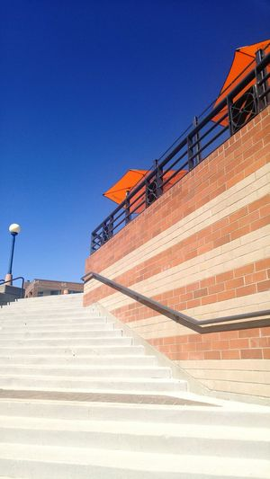 Steps by brick wall against clear blue sky