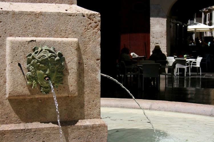 Throw a coin to the fountain to return one day to Valencia. Bronze Head Fountain Hidden Gems  Plaza Redonda, Valencia, Spain Restaurant Terrace Tables And Chairs Terrace Valencia, Spain My Favorite Place The City Light