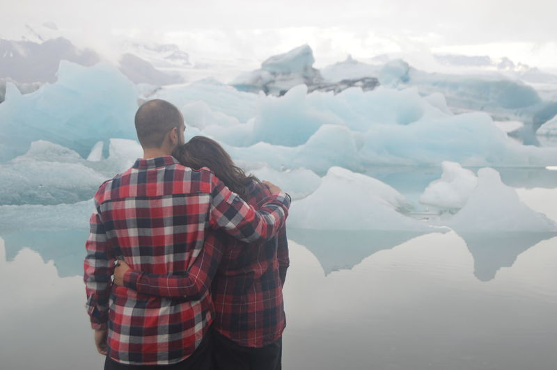 Rear view of couple standing on snow covered mountain