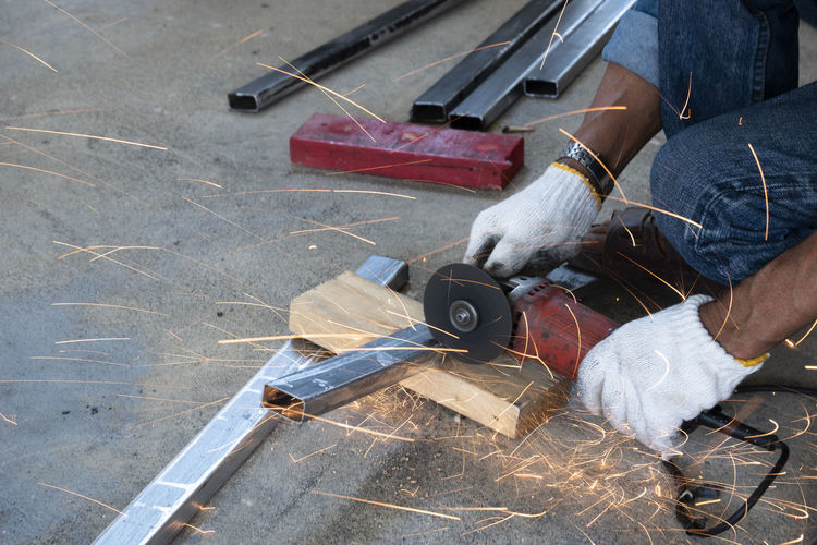 Low section of industrial worker cutting metal with hand saw