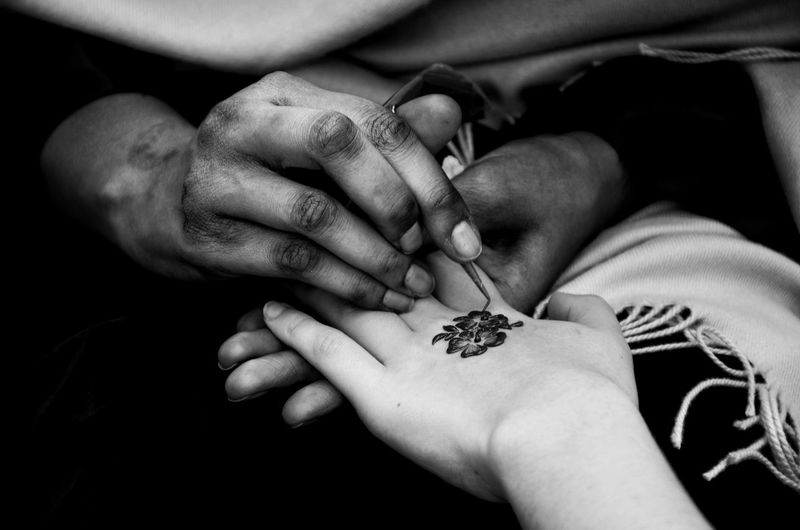 Close-Up Of Woman Receiving Henna Tattoo On Hand