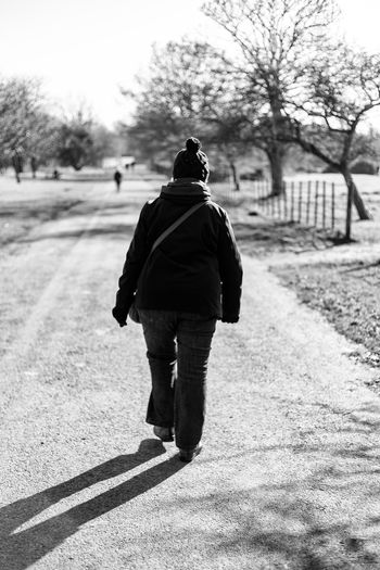 Blackandwhite Photography Country Road Walking Around Adult Cold Days Day Focus On Foreground Full Length Nature One Person Outdoors People Real People Rear View Road Senior Woman Sky Tree Walking Warm Clothing