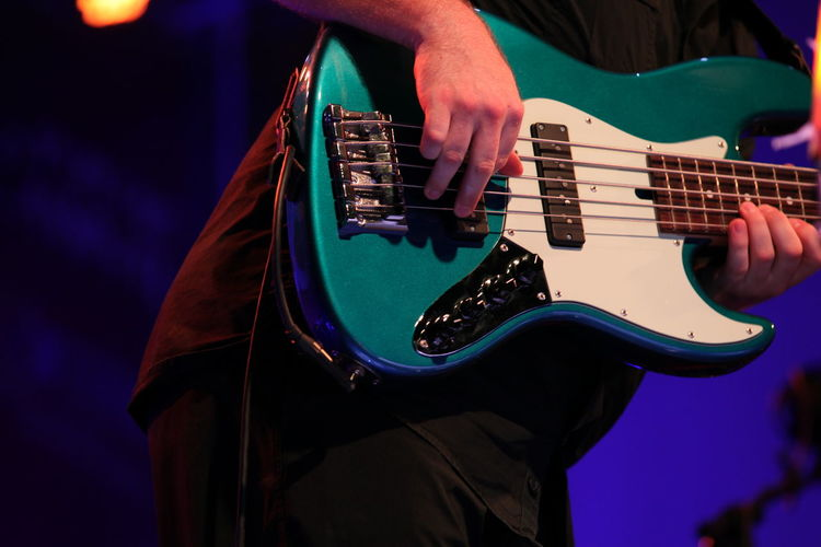 Midsection Of Man Playing Bass Guitar