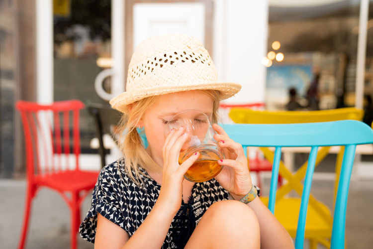 Cute girl drinking juice at outdoor restaurant