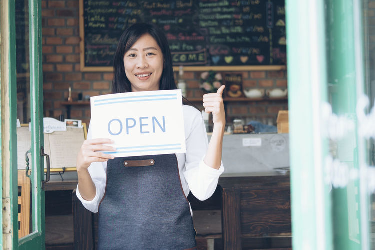 Portrait of female owner holding open sign while standing at doorway in cafe
