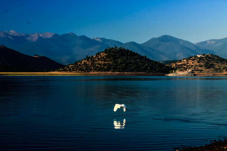 Scenic view of calm lake against mountain range