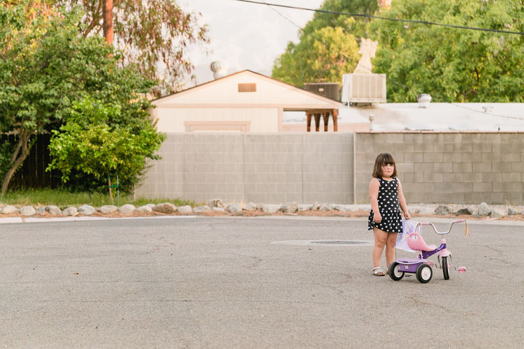 Girl Standing By Tricycle On Road