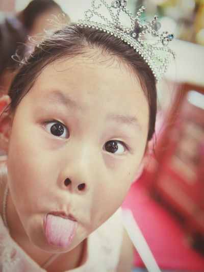 Close-up portrait of girl wearing tiara sticking out tongue