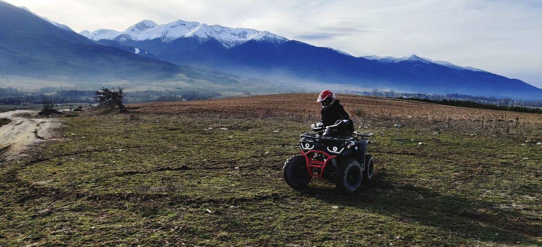 Man sitting on quadbike on field against sky