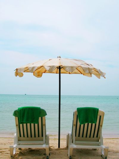 Two beach chairs with towels and beach umbrella on the beach close to the sea Sea Beach Island Rayong Thailand Holiday Vacation Weekend Couple Two Persons Summer White Sand Privacy Quite Recharge Relaxing Relaxation Activity Umbrella Towel Resort Hotel Destination Freedom Lifestyle