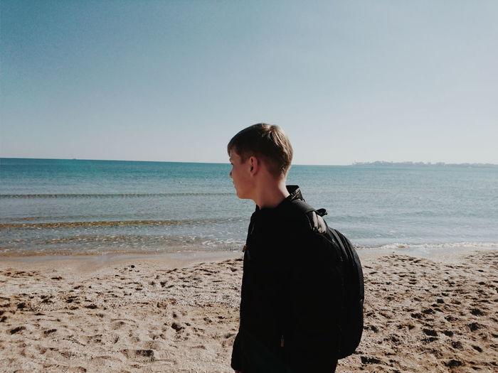 Teenage girl standing on beach against clear sky