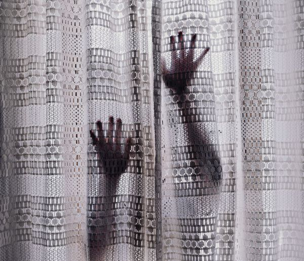 Woman touching curtain at home