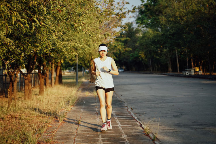 Woman runner does jogging on the city road. Sport and workout. Sport Workout Jogging Running Exercise One Person Full Length Plant Tree Real People Young Adult Front View Lifestyles Leisure Activity Casual Clothing Fashion Young Women Day Footpath Nature Standing Clothing Focus On Foreground Outdoors Beautiful Woman