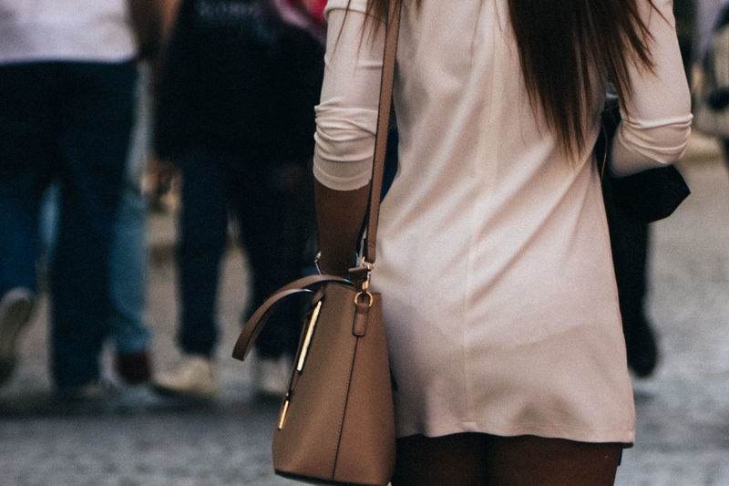 Midsection of woman with purse while walking on street