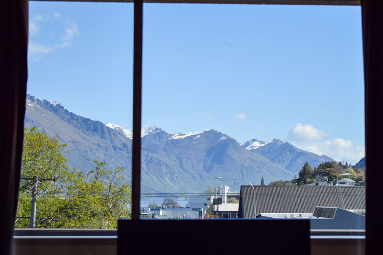 Scenic view of snowcapped mountains against sky seen through window