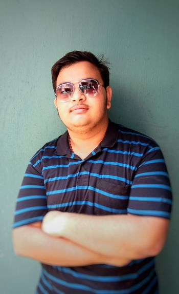 Close-up of young man with arms crossed wearing sunglasses while standing against wall