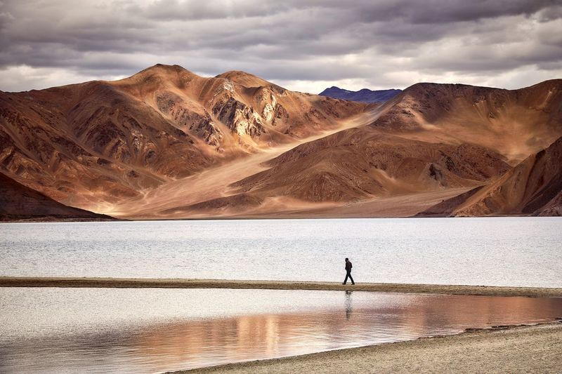 Distant view of silhouette man walking on footpath in lake against mountains