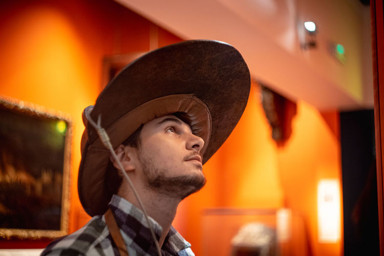 Young man wearing the vintage firefighter hat exhibited in the Museum of London Headshot Clothing Portrait Hat One Person Adult Side View Looking Young Adult Men Young Men Contemplation Profile View Brigade Fire Fighter Fire Brigade Vintage Old