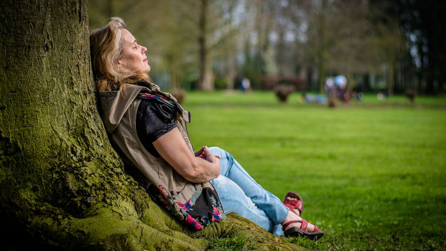 Woman Sitting By Tree Trunk At Park